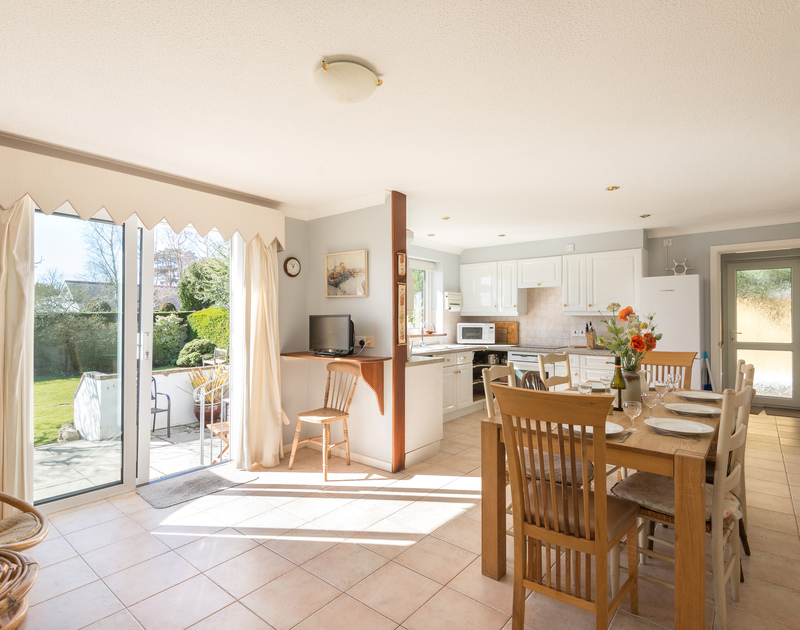 The french doors to the patio and garden in the open plan kitchen/dining room at The Garden House, a holiday rental in Rock, Cornwall.