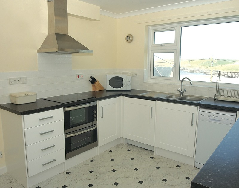 Light-filled, modern kitchen at Zapadiah, holiday accommodation in Polzeath, Cornwall with its view over the beach.