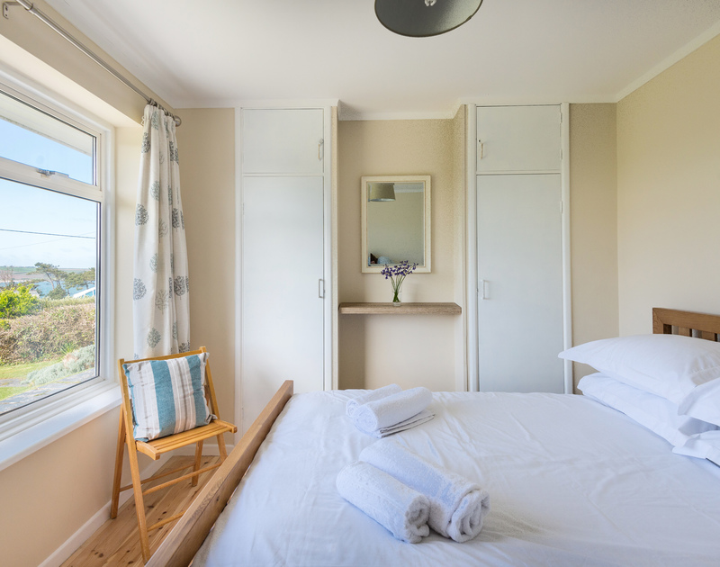 The ground floor double bedroom  at self catering holiday property Dolphins looking out onto the garden and the Camel Estuary glistening through the trees.