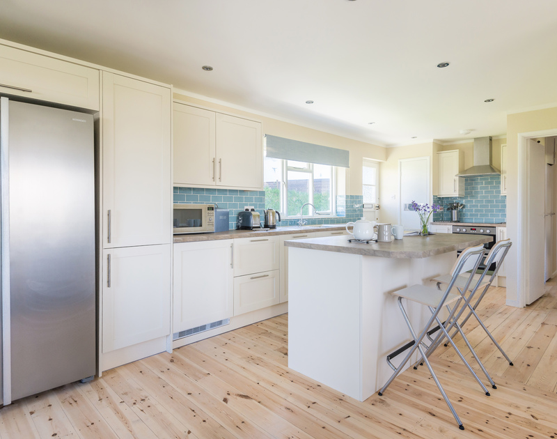 Tasteful, coastal blues and clean, bright whites decorate the kitchen at Dolphins above Daymer Bay  in Cornwall.