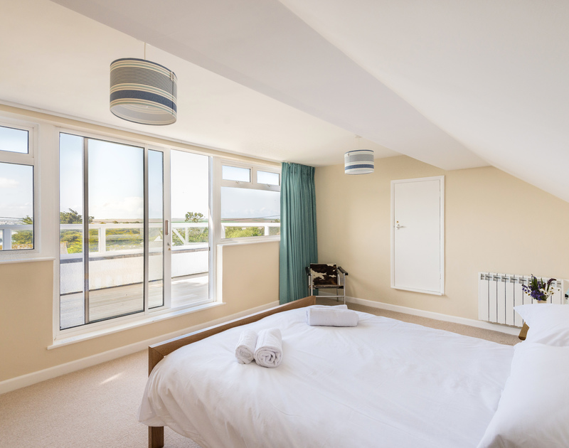 The sliding glass doors fill the master bedroom with light at holiday property Dolphins.