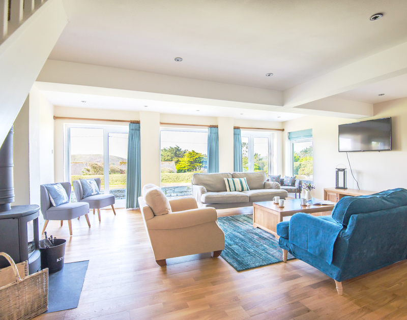 The sitting room is full of light flowing in from the huge amount of glass at self catering, coastal, holiday retreat Dolphins in north Cornwall.