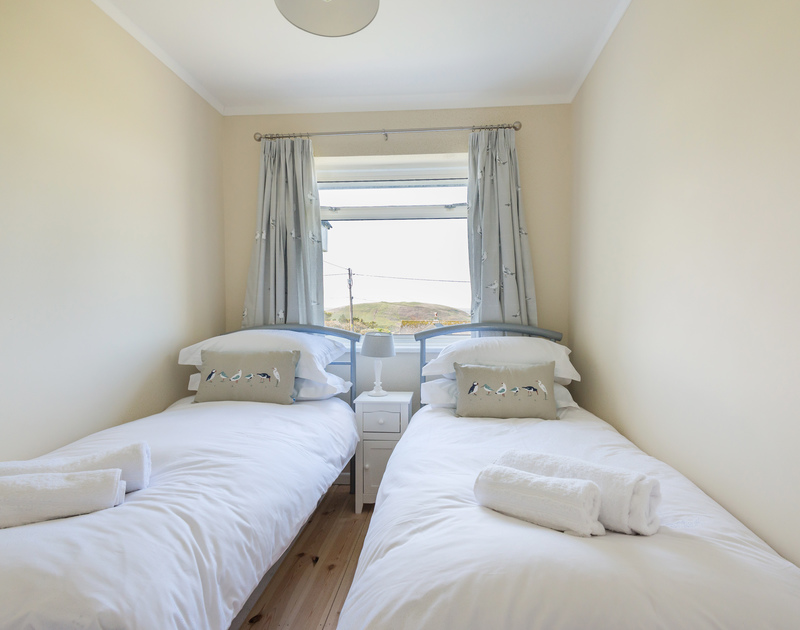 The twin bedroom with coastal birds on the furnishings and Brea Hill framed by the window at Dolphins, a self catering hoilday house on the north Cornish coast.