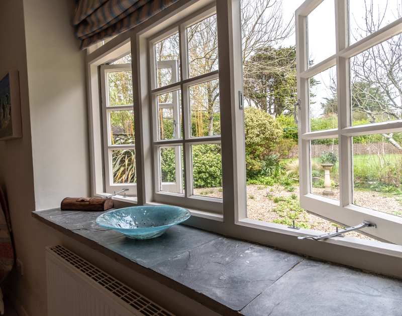 Wide, slate windowsill and pretty wooden windows frame the garden outside at self catering, holiday property Greystones, in north Cornwall.