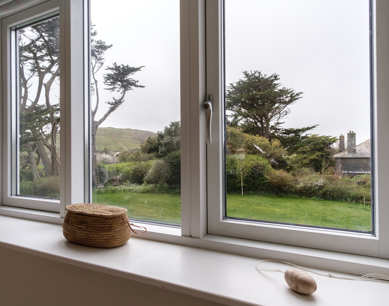 Garden view from the window of self catering holiday house Greystones with the sandy  footpath tracking up Brea Hill beyond.