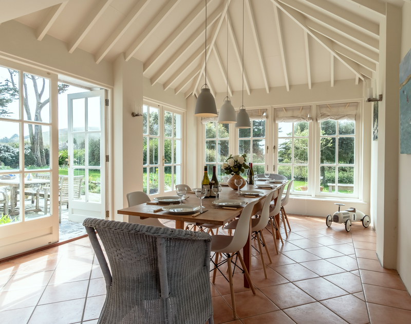 a large glass room with a wooden roof with patio doors leading out onto the bright and sunny garden