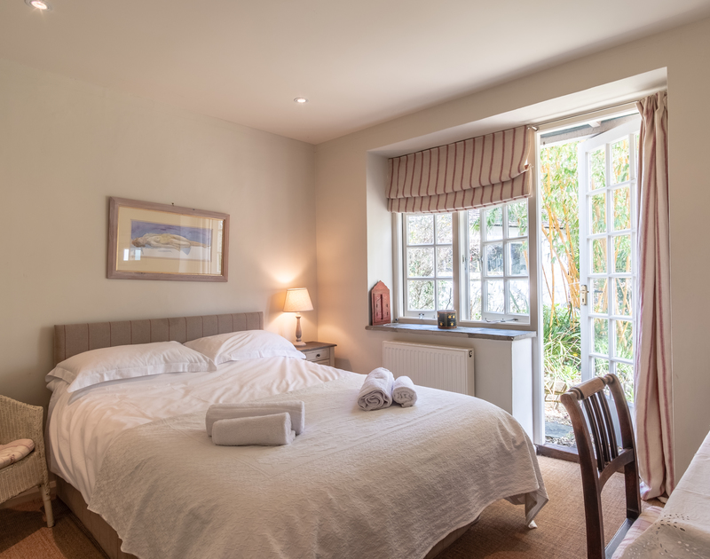 The tranquil, ground floor king size bedroom at Greystones has a door leading out to the pretty garden close to the beach at Daymer bay.