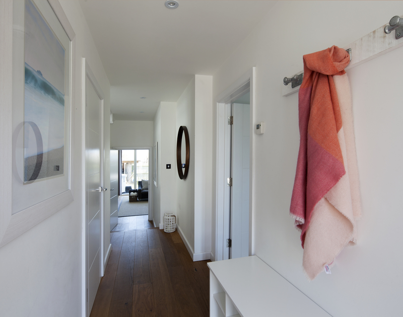The bright hallway with warm wooden flooring at 2, The Sands, a self catering holiday house to rent in Polzeath.