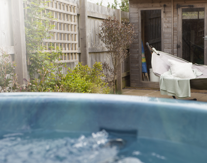 The hot tub and patio and outside eating area at 2 The Sands, a luxury self catering holiday home in Polzeath, Cornwall.