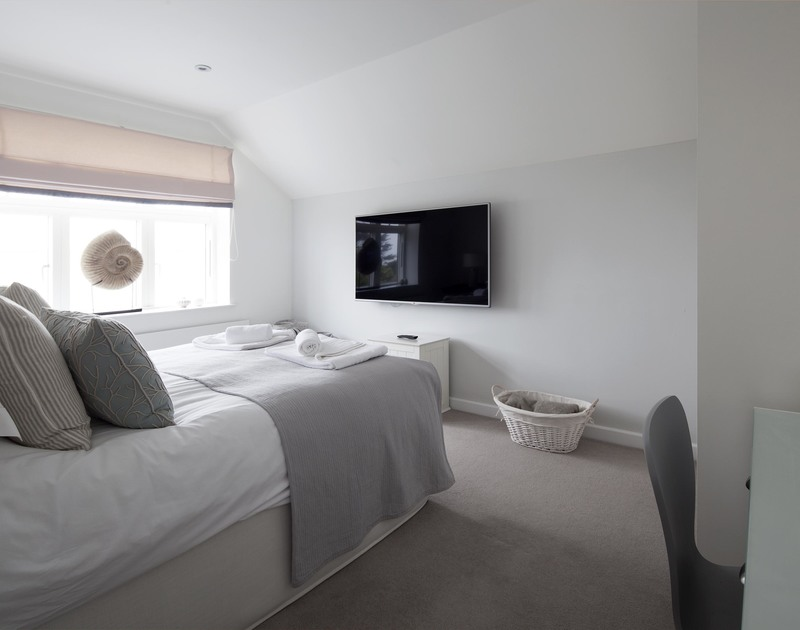 A flat screen TV on the wall in one of the king size bedrooms at 2, the Sands, luxury holiday accommodation in Polzeath.