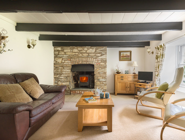The cosy sitting room and open fireplace in Old Kea Cottage, a self catering holiday rental in Rock, North Cornwall.