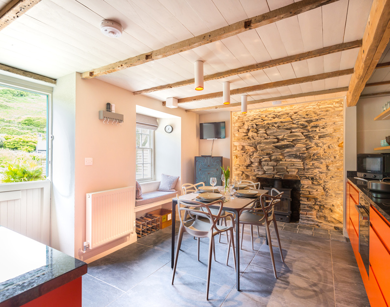 The feature exposed Cornish wall and wood burner in the modern open plan kitchen/dining room at Crow's Nest, a fabulous bolthole in the seaside village of Port Isaac.