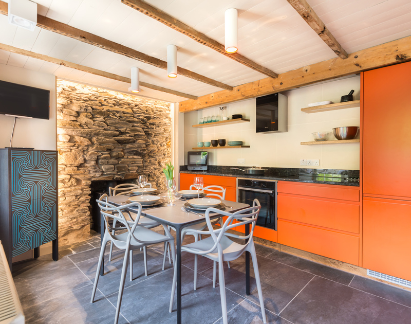 The cool, orange modern kitchen has exposed beams, stonework and a slate floor mingling together perfectly in the open plan lower ground floor at Crow's Nest in Port Isaac.