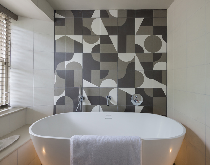 Freestanding bath and a feature tiled wall in the bathroom at Crow's Nest a recently refurbished Fishermans cottage with luxurious modern comforts in Port Isaac.