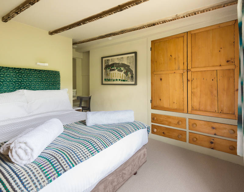 Calming colour palette with exposed beams and  a good sized cupboard in the comfortable double bedroom at Crow's Nest in Port Isaac in Cornwall.