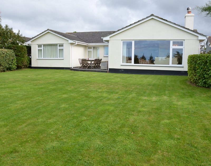 The lawned rear garden at Trewin, a self catering holiday property to rent in Rock, Cornwall.