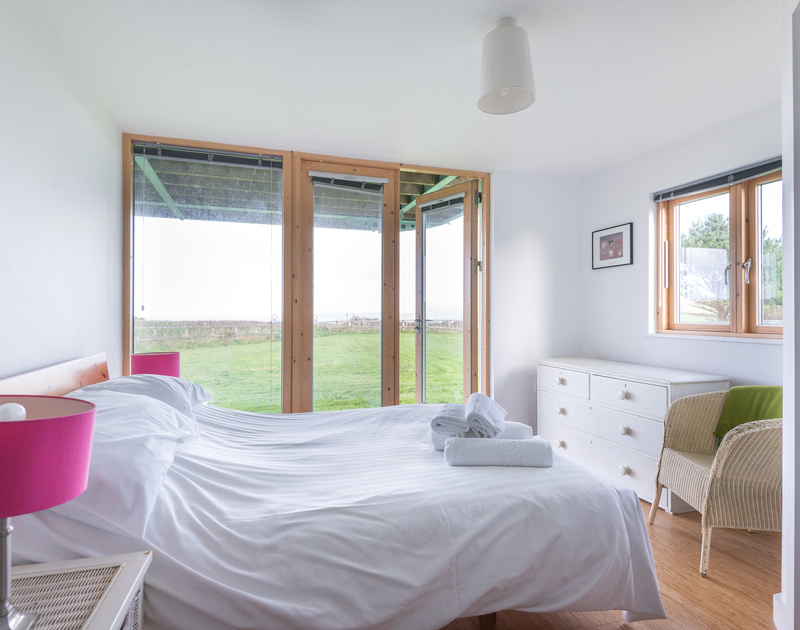 Plenty of natural light throughout the double bedroom from the window and french doors leading out to the garden at North Light in Port Isaac.