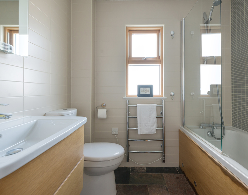 A stylish bathroom with bath and shower at North Light, a self catering holiday house to rent on the North Cornish Coast overlooking Port Isaac.