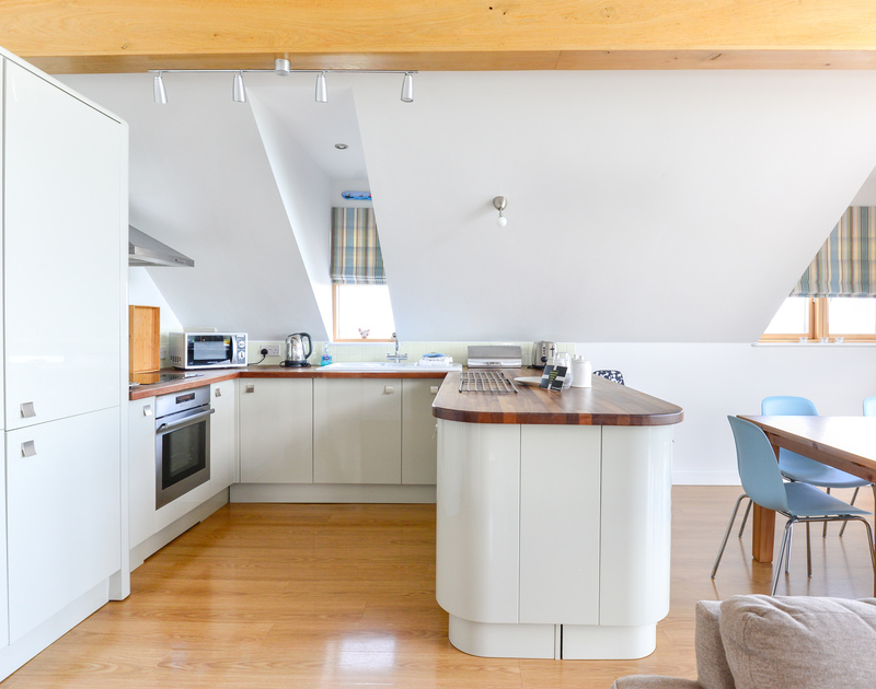 The kitchen on the open plan first floor at North Light is bathed in natural light, in this truly unique self catering holiday home in Port Isaac in North Cornwall.