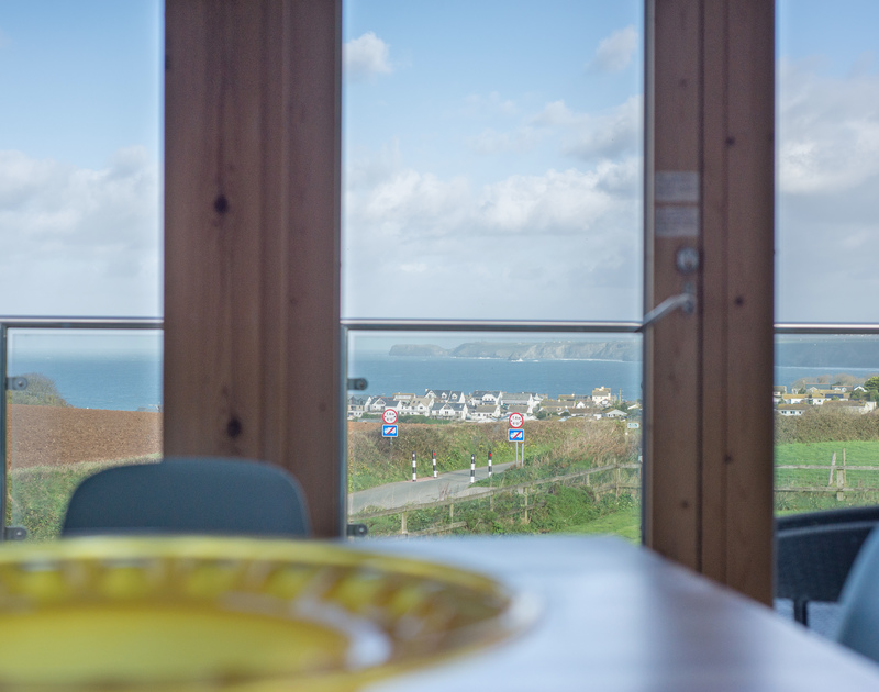 The dining table at self catering holiday house North Light has stunning views over Port Isaac and then out to sea along the North Cornish coastline.