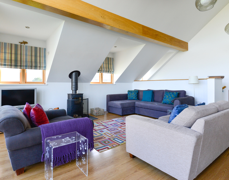 Retire towards the wood burner and sofas in the living room at North Light after busy days exploring the nearby beaches, coastal paths or the pretty harbourside village of Port isaac.
