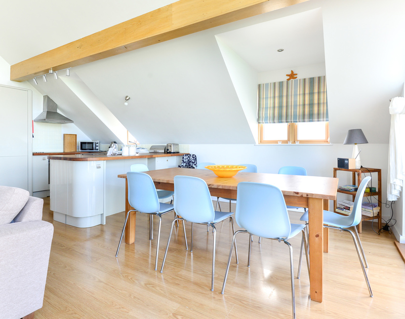 The dining room on the open plan first floor with panoramic sea and coastal views over Port Isaac in North Cornwall.