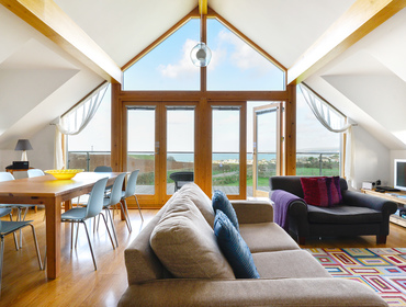 The floor to vaulted ceiling glass windows and doors make the most of the panoramic sea, coastal and countryside views from reversed level unique holiday house North Light in Port Isaac in Cornwall.