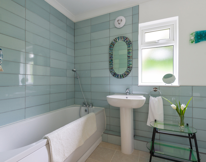 Sea blue tiling in the family bathroom at self catering holiday house to rent Sliggon Field set in beautiful gardens in Trebetherick.