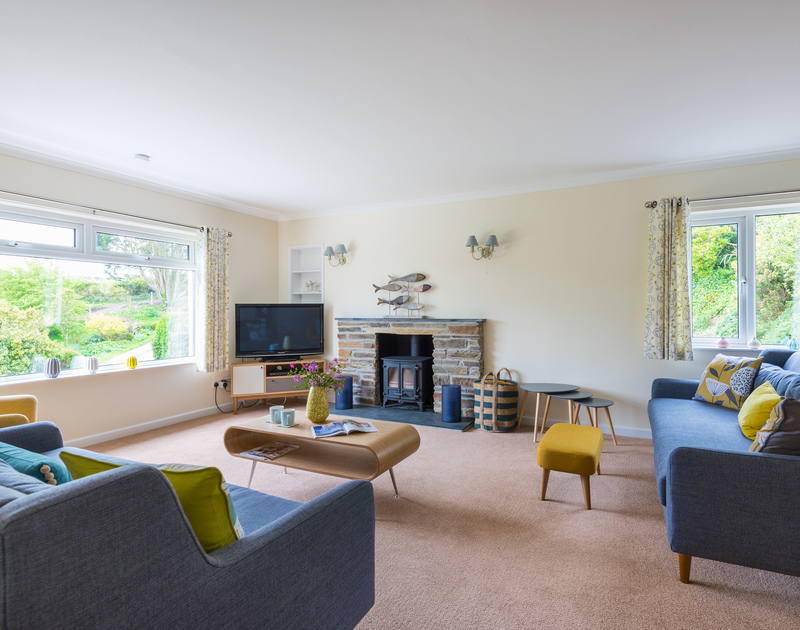 The stylish sitting room with woodburner at Sliggon Field, a self catering, holiday house to rent close to the sea set within beautiful gardens in Trebetherick.