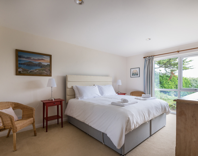 The elegant master bedroom with huge windows letting the light flood in at holiday house Tringa in Daymer Bay.