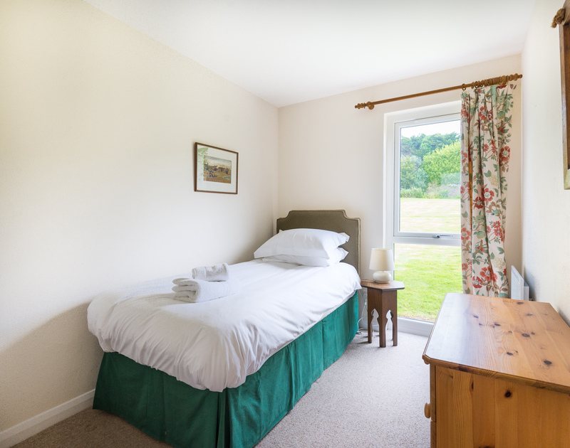Single bedroom at Tringa with a large window overlooking the garden, close to the beach at Daymer Bay in north Cornwall.