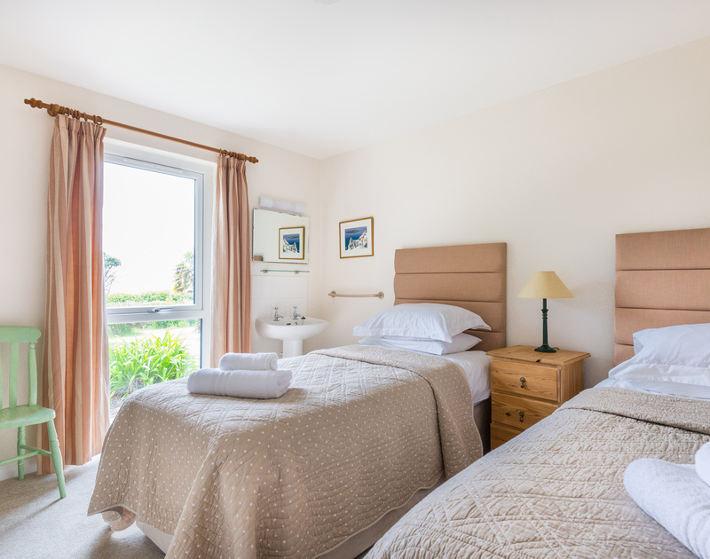 One of the three twin bedrooms with views of the garden from the window at Tringa in Daymer Bay.