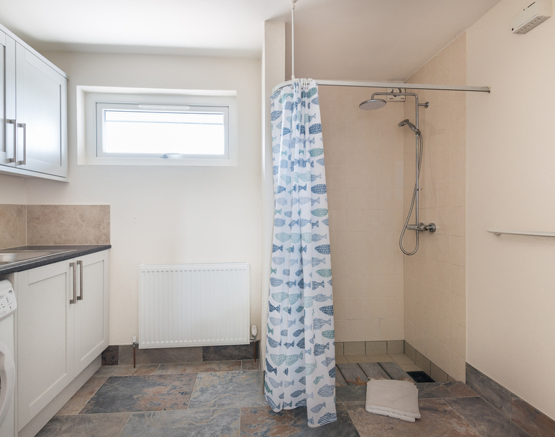 Useful utility room with shower and WC at Tringa, a seaside holiday house to rent in Daymer Bay.