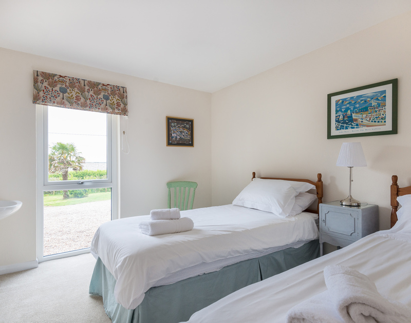 One of three twin bedrooms with a basin at holiday rental Tringa with a large window overlooking the front garden.