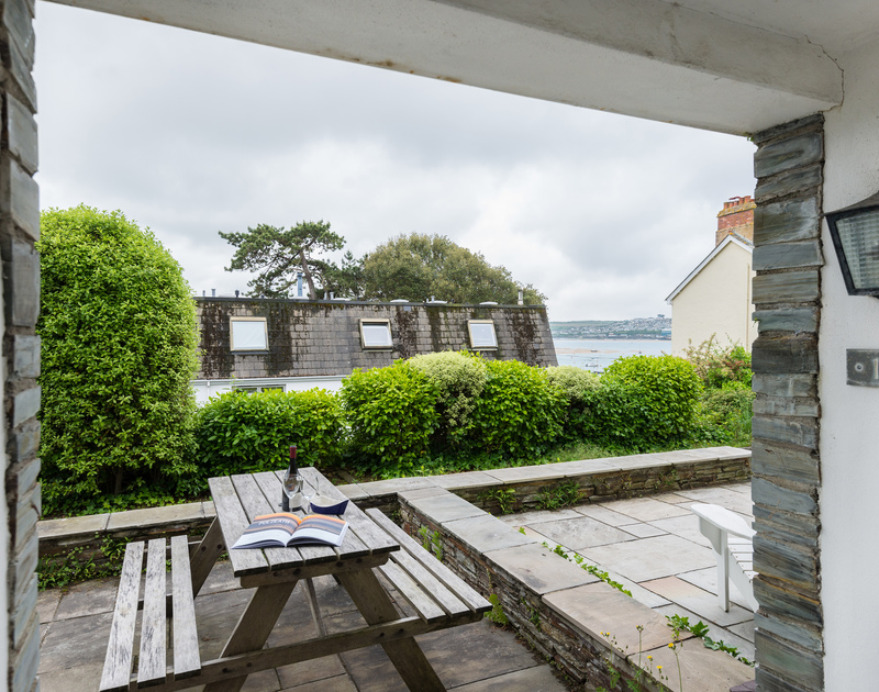 The picnic table and small paved terrace of Slipway 10, holiday accommodation in Rock, Cornwall