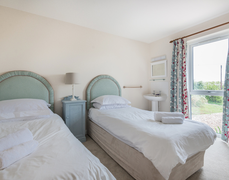 Another pretty twin bedroom with a basin at Tringa, a self catering, holiday rental in Daymer bay.