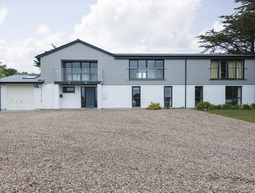The large graveled driveway and attractive part clad exterior of Tringa, a holiday house, just a short walk away from the sea and sands of Daymer Bay in north Cornwall.