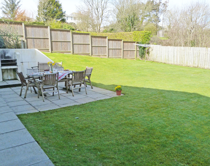 The large patio area and lawned garden at Penina, a self catering holiday rental in Polzeath, North Cornwall.