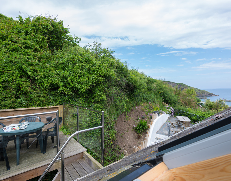 The decking at self catering holiday accommodation April Cottage has views of the headland, sea and the harbour side village of Port Isaac in North Cornwall.