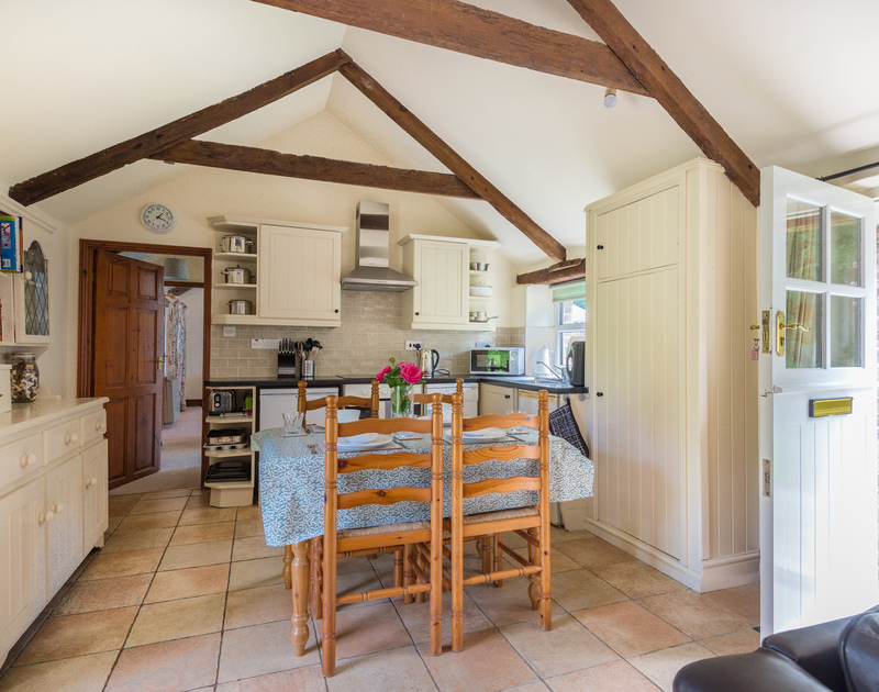 Well appointed, characterful kitchen and dining table in pretty open plan Millers Cottage.