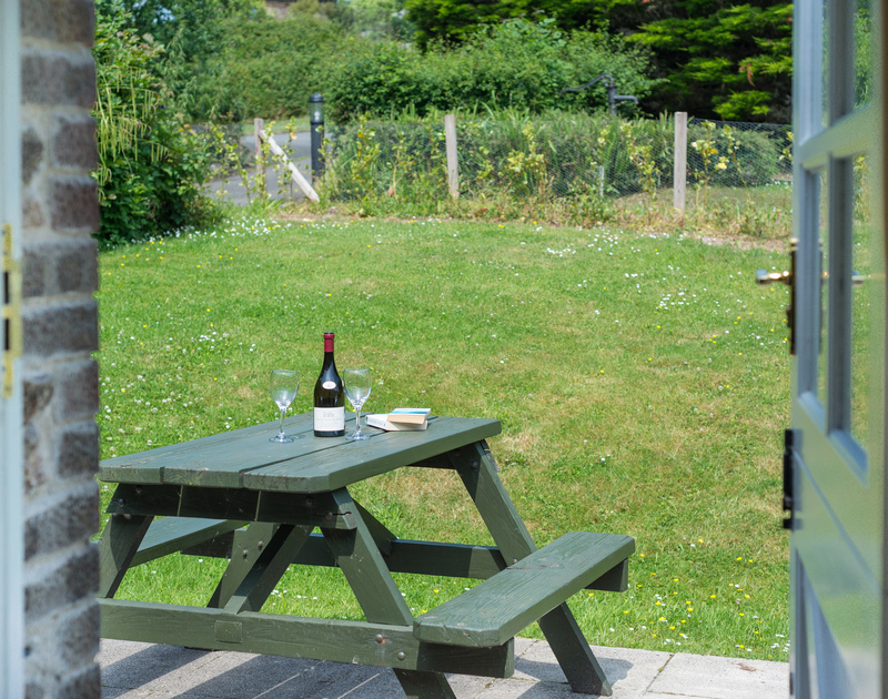 Enjoy a glass on the picnic table in the garden at self catering Millers Cottage, an ideal, pet friendly retreat near St Minver in North Cornwall.