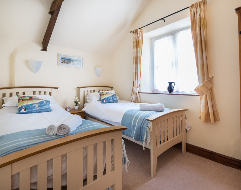 Lovely twin bedroom with a vaulted ceiling and original beams at pretty country style holiday rental Millers Cottage a few miles drive from the North Cornish Coast.