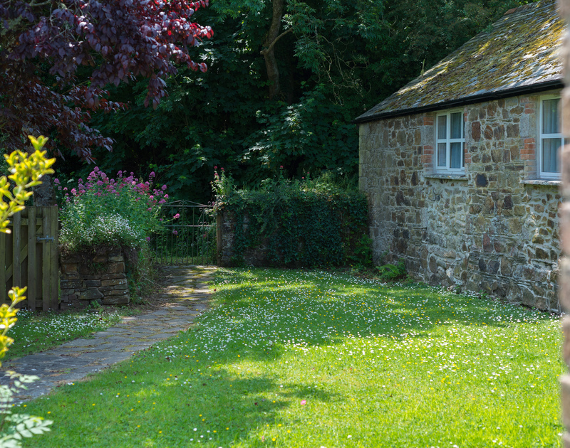 Gorgeous stone exterior of self catering, holiday retreat Millers Cottage in the pretty country garden near St Minver in North Cornwall.