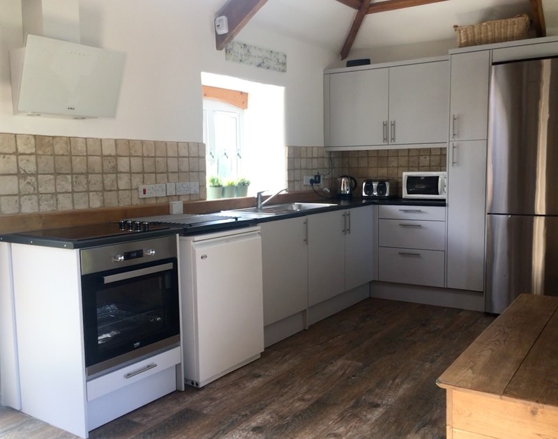 The galley style kitchen end of the open plan living space in An Skyber Barn, Polzeath.