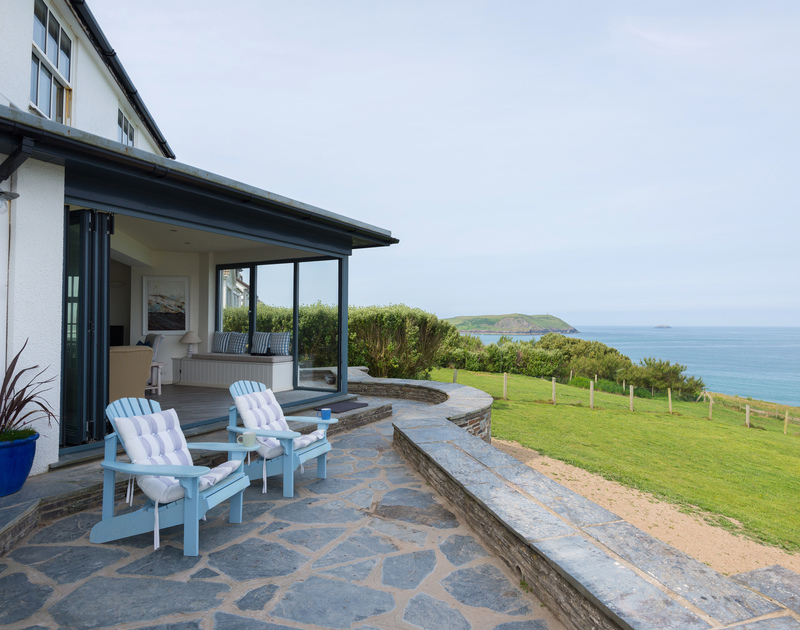The patio furniture on the terrace with sea views of Stepper point and the garden at Treviles, a holiday house in a magnificent setting on the cliffs at Polzeath in North Cornwall.