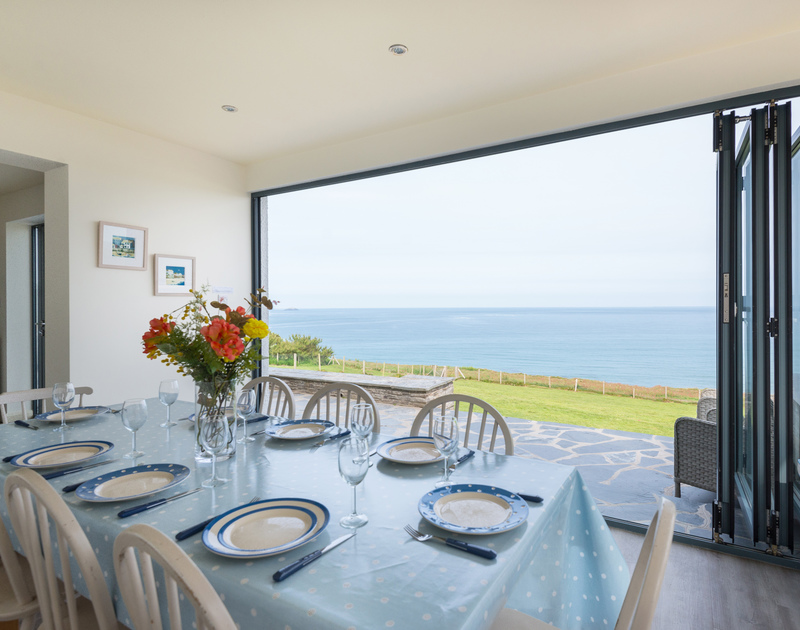 Unforgettable family meals, a stones throw from the ocean at self catering, holiday property, Treviles, where bi-fold doors open completely out to the garden, clifftop and sea beyond.