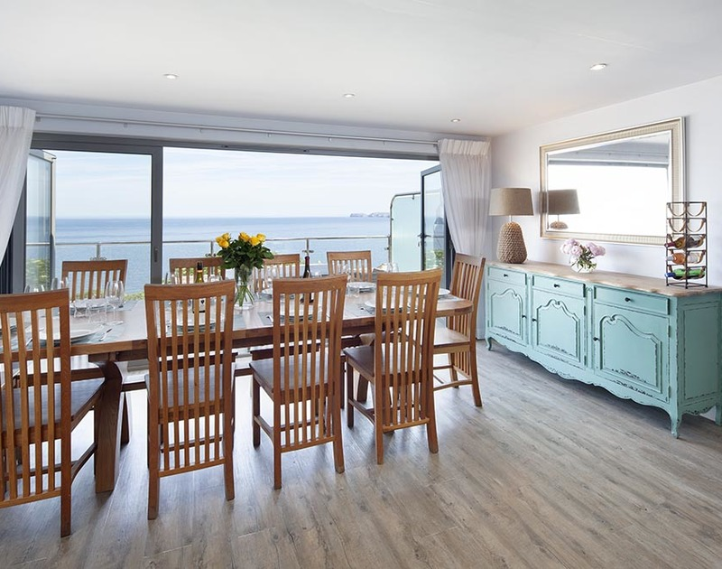 Soak up stunning sea views from the open plan dining room and balcony at The Crows Nest, Port Isaac