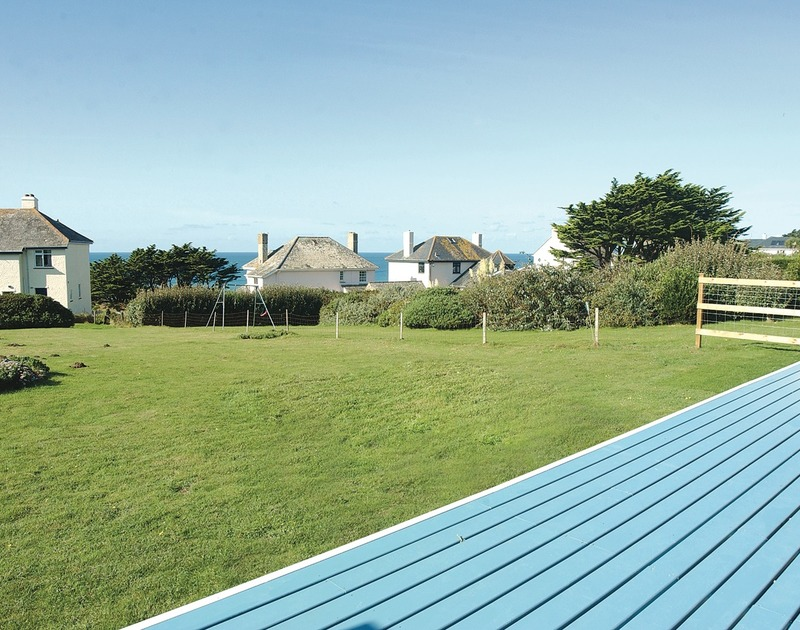 Sea views from the deck of Rock Pipit, a superb holiday house at Polzeath, Cornwall, with large lawn in the foreground.