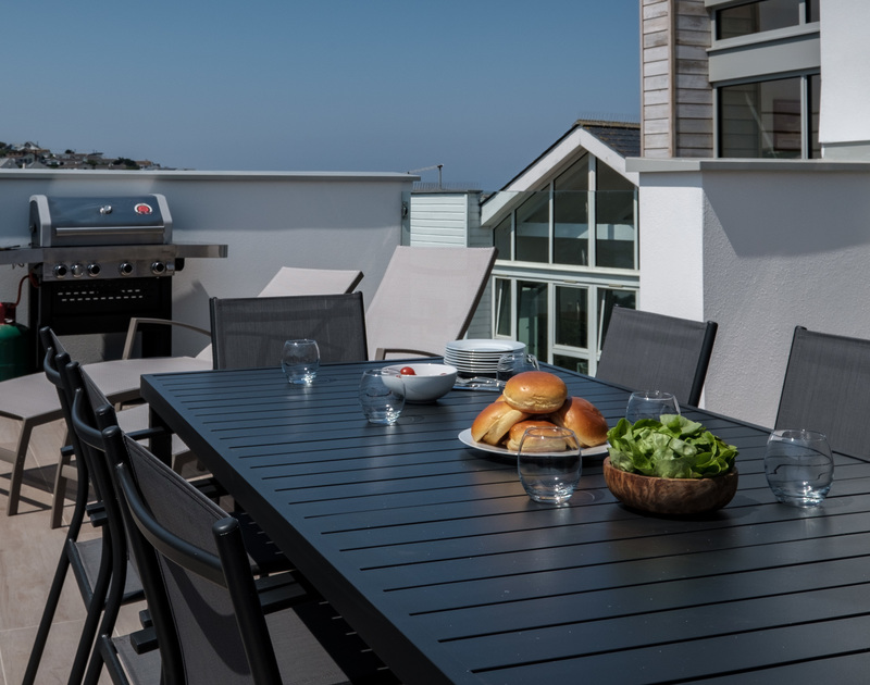 The sheltered balcony at Point Break is the perfect spot for a family barbeque in Polzeath, North Cornwall.
