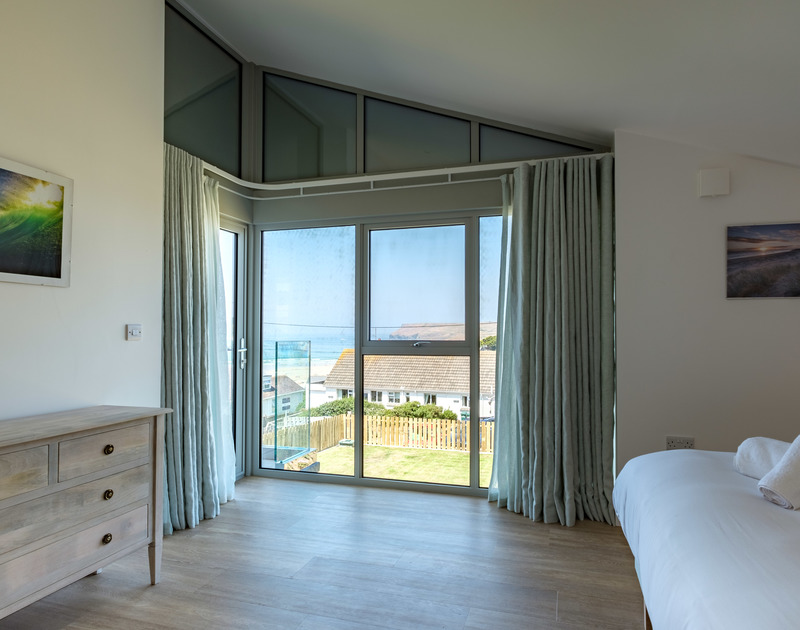 Light pours into the master bedroom at Point Break from the cleverly designed glass,windows and door in the corner making the most of the sea views over Polzeath.